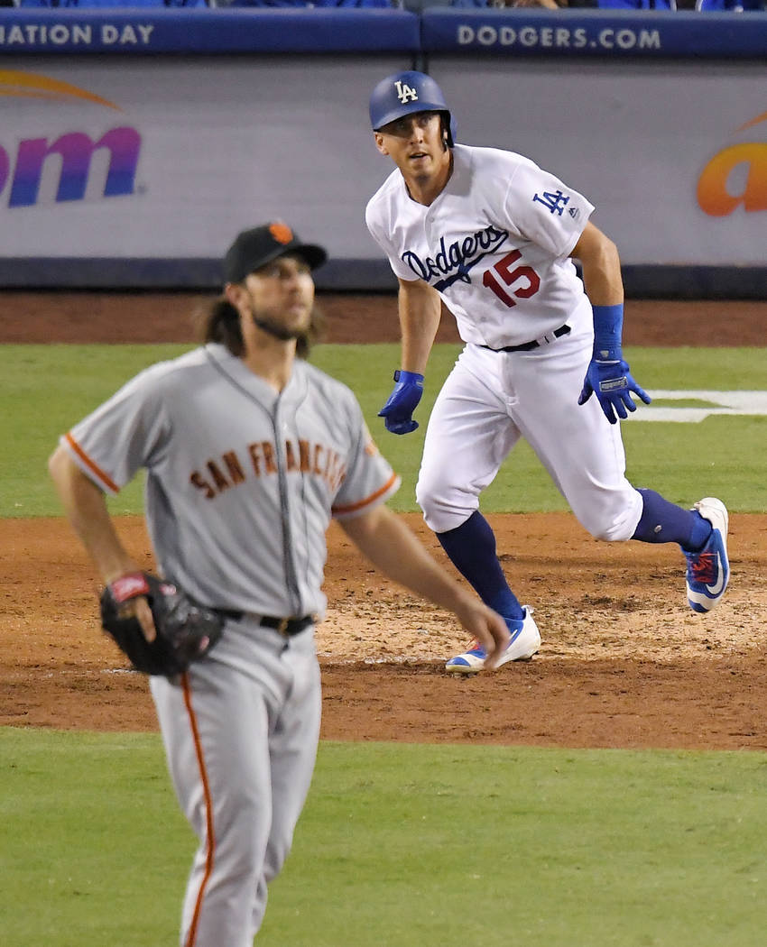 Los Angeles Dodgers' Austin Barnes, right, runs to first after hitting a solo home run while San Francisco Giants starting pitcher Madison Bumgarner watches during the eighth inning of a baseball  ...