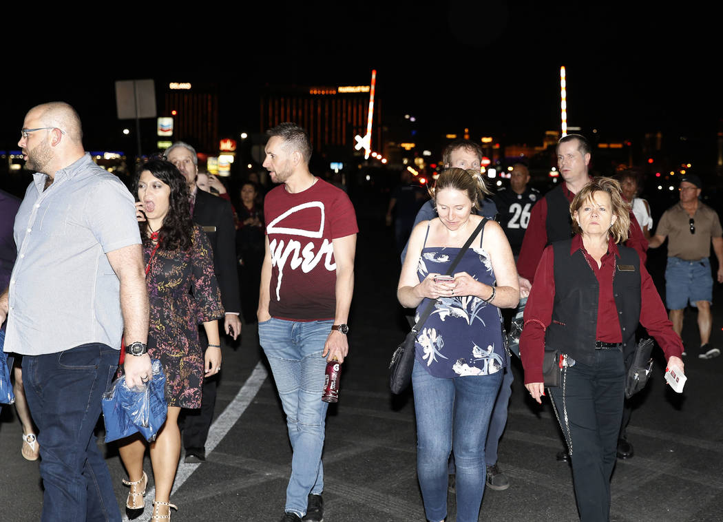 People who have been evacuated from Mandalay Bay hotel-casino walk on Las Vegas Boulevard as Las Vegas police respond during an active shooter situation on the Strip on Sunday, Oct. 2, 2017, in La ...