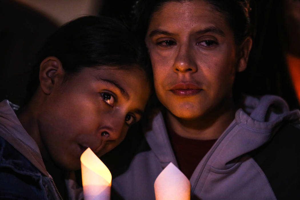 Jocelyn Morales, 12, and Monica Lopez-Morales, 43, of Las Vegas gather during a vigil near the Town Square Las Vegas in remembrance of the Mandalay Bay shooting victims in Las Vegas, Monday, Oct.  ...