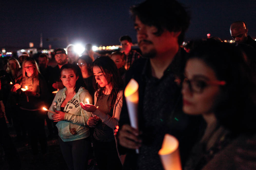 People gather at a vigil near the Town Square Las Vegas in remembrance of the Mandalay Bay shooting victims in Las Vegas, Monday, Oct. 2, 2017. The shooting took place Sunday night and killed at l ...