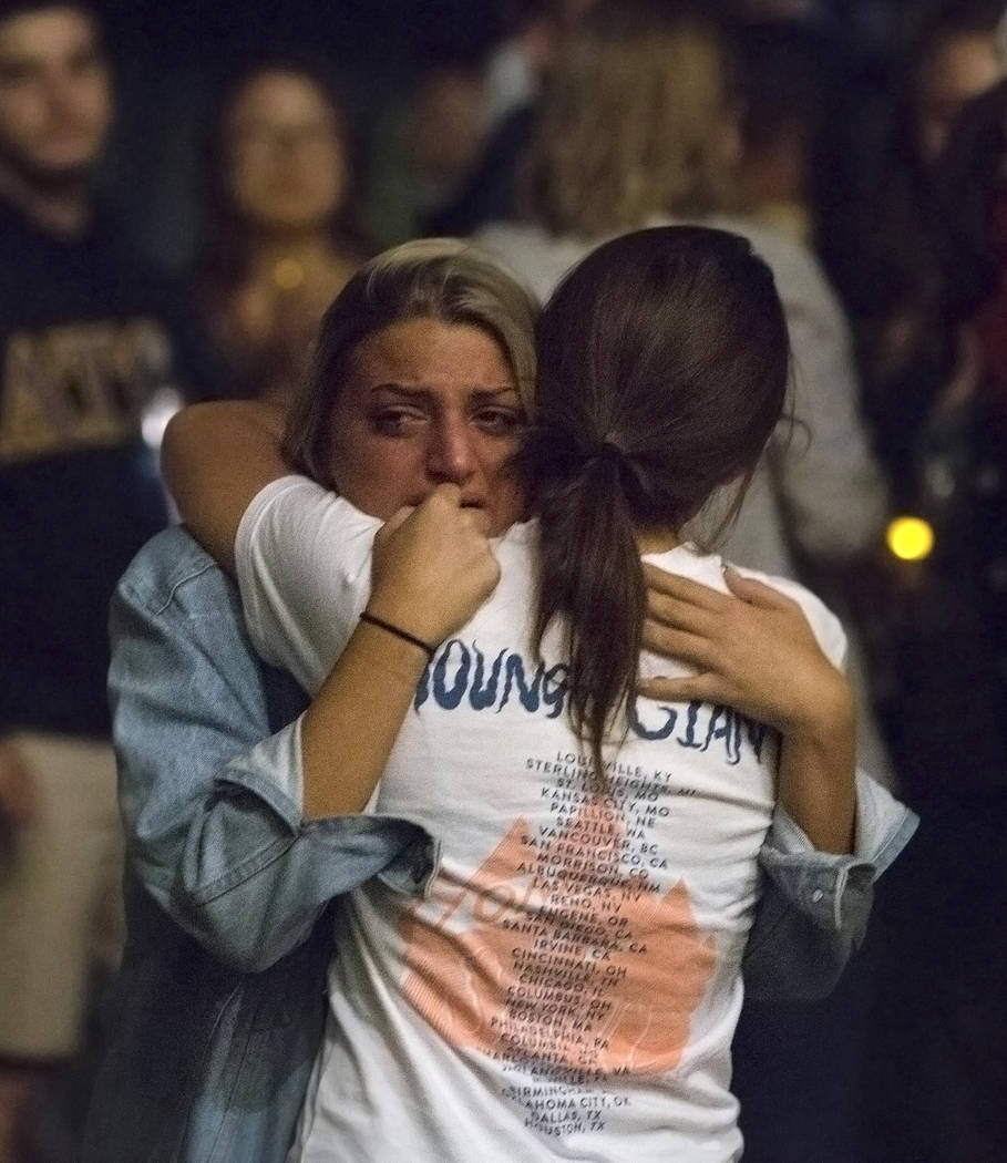Attendees of a vigil for the shooting victims of the Route 91 country music festival share a hug on Monday, October 2, 2017, at the Student Union courtyard, at UNLV, in Las Vegas. A gunman in a Ma ...