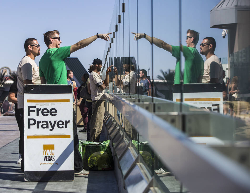 Martin Malmberg, middle/left, talks and prays with crowds of onlookers near Las Vegas Boulevard and Tropicana Avenue on Monday, October 2, 2017, after a gunman in a Mandalay Bay hotel room shot in ...