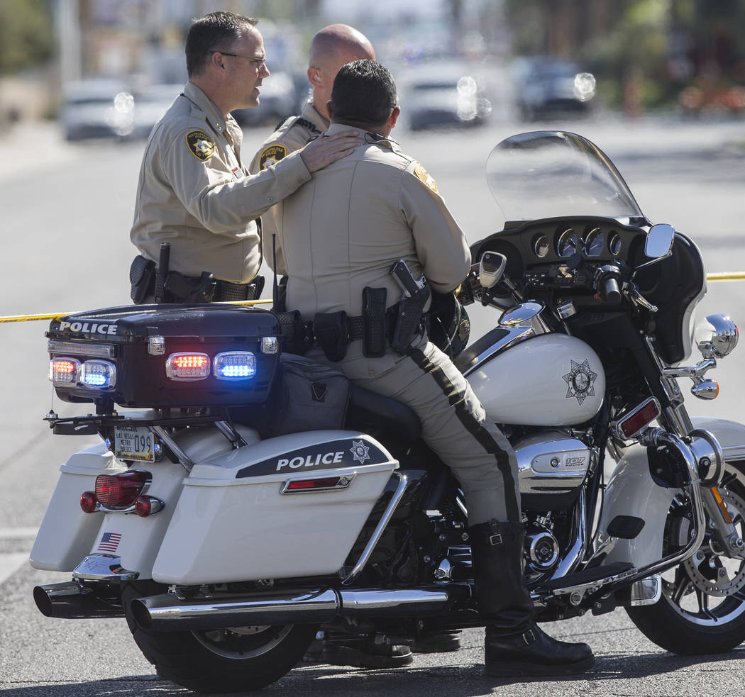 Metro officers console each other while directing traffic on Las Vegas Boulevard and West Reno Avenue across from the Mandalay Bay hotel/casino on Monday, October 2, 2017, after a gunman in one of ...