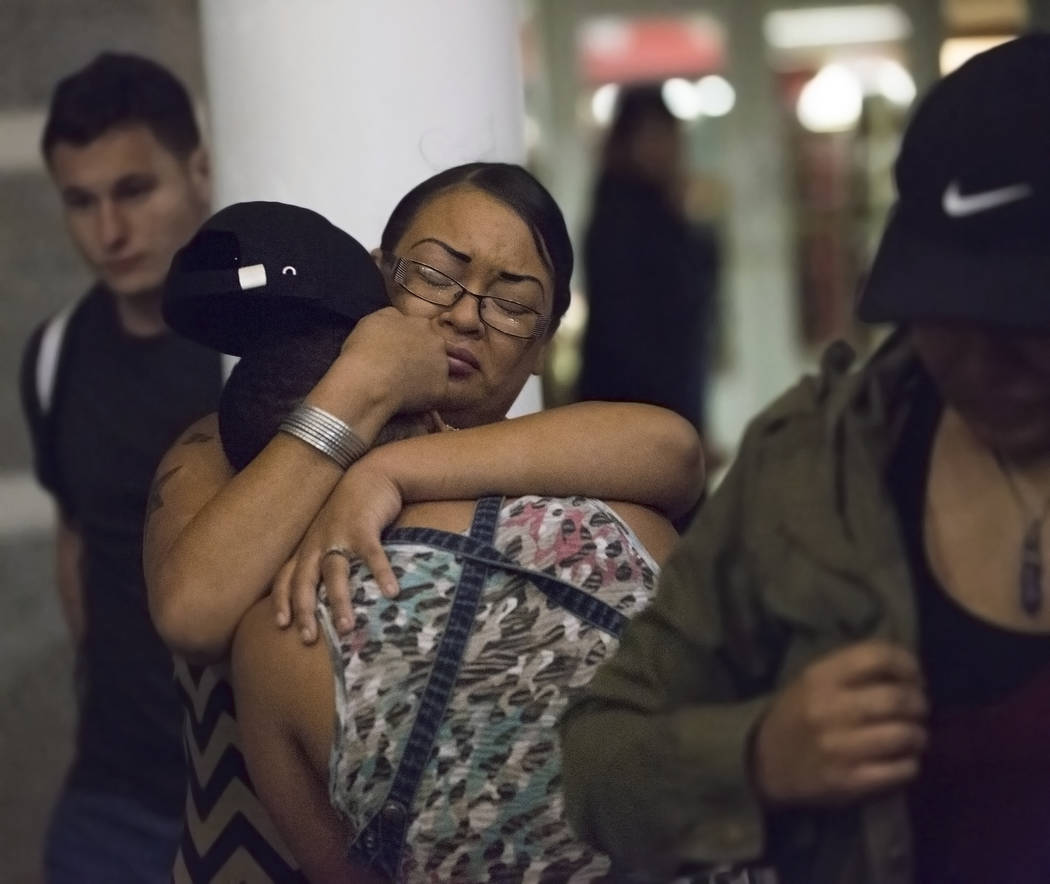 Raenna Harper, middle, gets a hug during a vigil for the shooting victims of the Route 91 country music festival on Monday, October 2, 2017, at the UNLV Student Union courtyard in Las Vegas. A gun ...