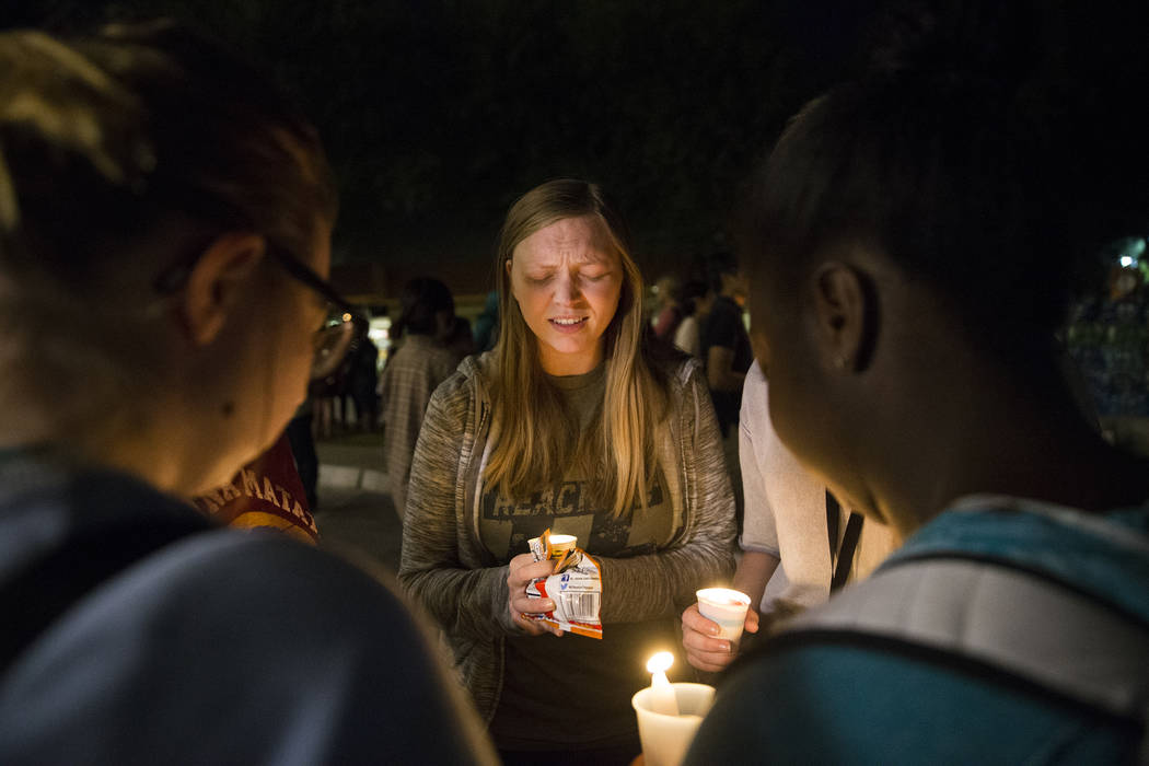 Kelly Lopez, middle, leads a prayer session during a vigil for the shooting victims of the Route 91 country music festival on Monday, October 2, 2017, at the Student Union courtyard, at UNLV, in L ...