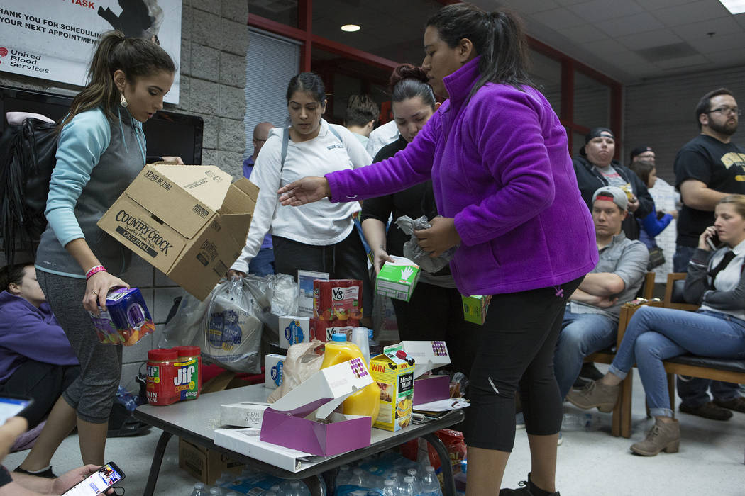 Judith Gonzalez, left and Emily Sandoval bring food donations to those that are waiting to donate blood at United Blood Services in Las Vegas Monday, Oct. 2, 2017, following a shooting on the Stri ...