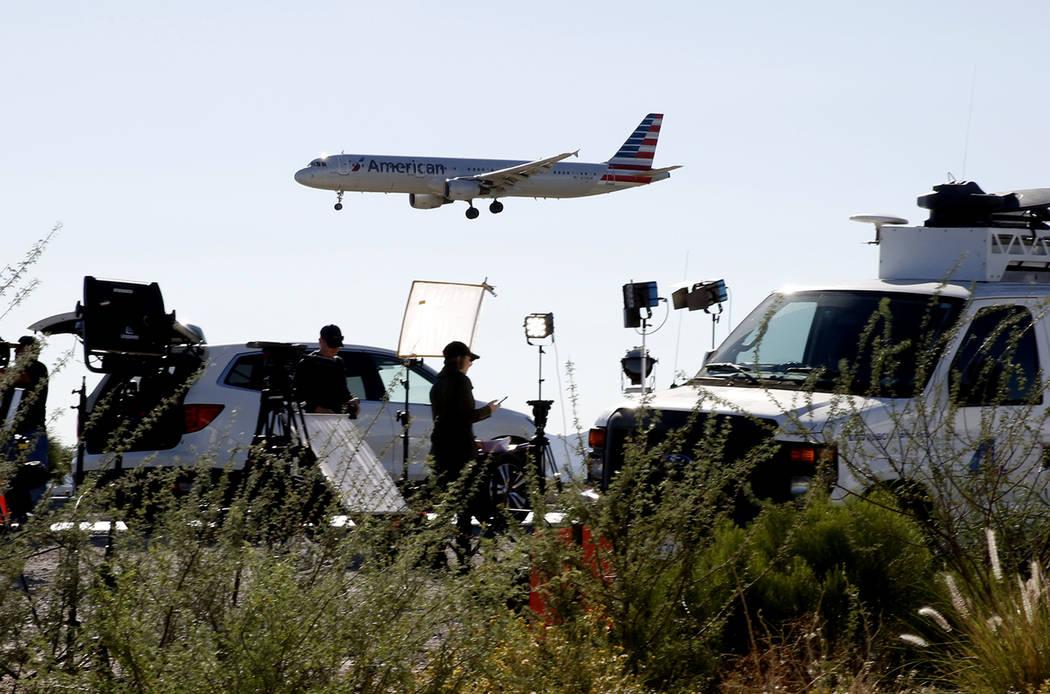An American Airways plane flies over TV satellite trucks near McCarran International Airport on Monday, Oct. 2, 2017, in Las Vegas. Bizuayehu Tesfaye Las Vegas Review-Journal @bizutesfaye