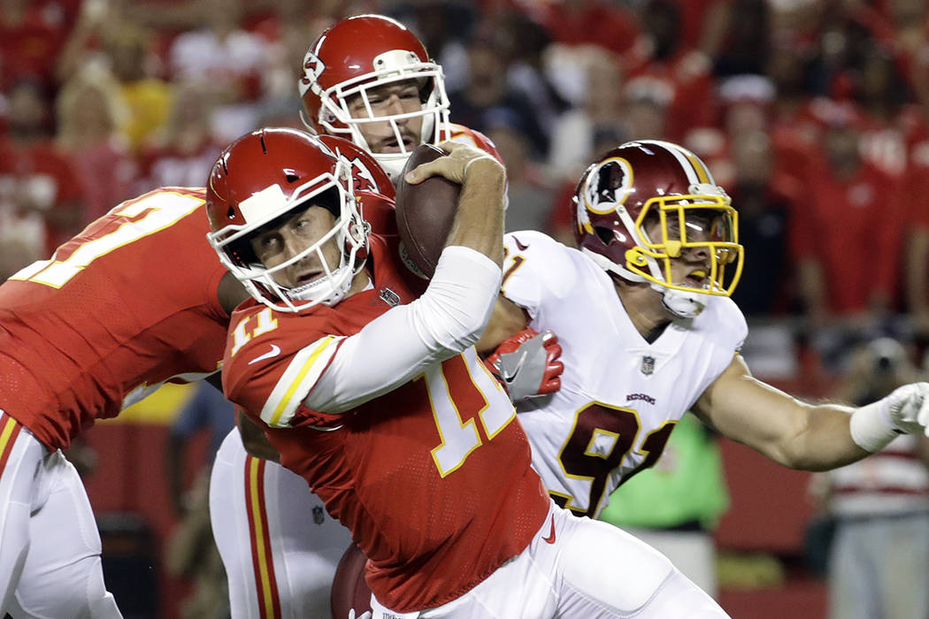Kansas City Chiefs quarterback Alex Smith (11) tries to avoid Washington Redskins linebacker Ryan Kerrigan (91) during the first half of an NFL football game in Kansas City, Mo., Monday, Oct. 2, 2 ...