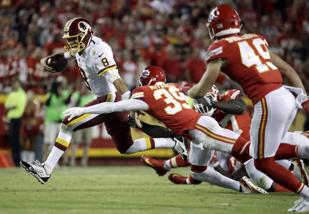 Washington Redskins quarterback Kirk Cousins (8) runs away from Kansas City Chiefs defensive back Terrance Mitchell (39) during the second half of an NFL football game in Kansas City, Mo., Monday, ...
