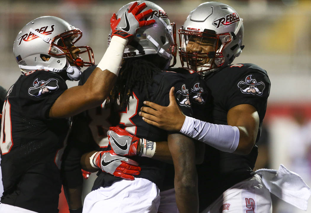 UNLV quarterback Armani Rogers, right, reacts after a touchdown by UNLV wide receiver Devonte Boyd, center, during a football game at Sam Boyd Stadium in Las Vegas on Saturday, Sept. 2, 2017. Chas ...