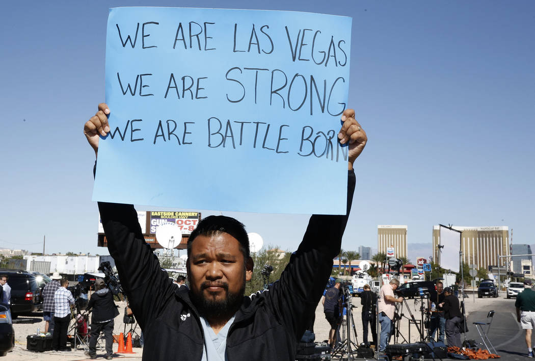 "Jon Dimaya, nurse at Sunrise Hospital, holds a sign that reads ""We are Las Vegas, We are Strong, We are Battle Born'' on Las Vegas Boulevard near Mandalay Bay hotel-casino on Monday, Oct. ..."