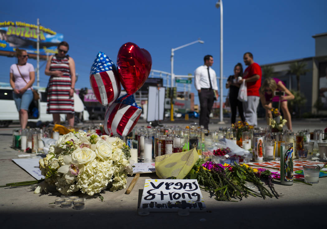 People take in a memorial at Las Vegas Boulevard and Sahara Avenue in Las Vegas during the early hours of Tuesday, Oct. 3, 2017. A gunman opened fire on attendees of a music festival Sunday night, ...