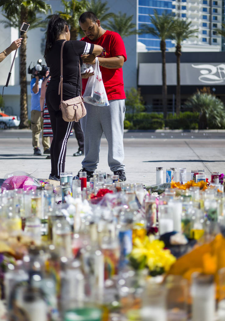 Las Vegas residents Elba Armendariz, left and David Robles light candles to leave at a memorial at Las Vegas Boulevard and Sahara Avenue in Las Vegas during the early hours of Tuesday, Oct. 3, 201 ...
