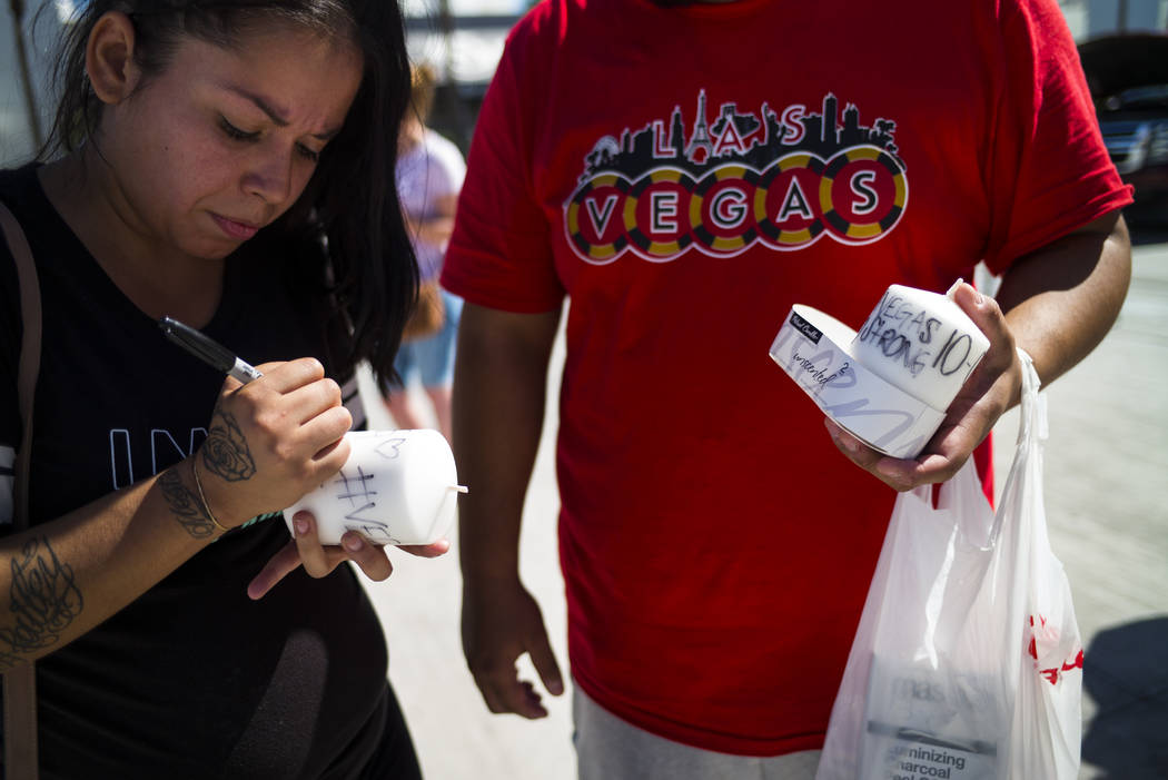 Las Vegas residents Elba Armendariz, left and David Robles prepare candles to leave at a memorial at Las Vegas Boulevard and Sahara Avenue in Las Vegas during the early hours of Tuesday, Oct. 3, 2 ...