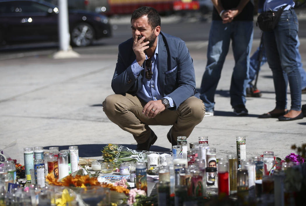 Antioch Carrillo pauses at a memorial after leaving flowers at Las Vegas Boulevard and Sahara Avenue in Las Vegas during the early hours of Tuesday, Oct. 3, 2017. A gunman opened fire on attendees ...
