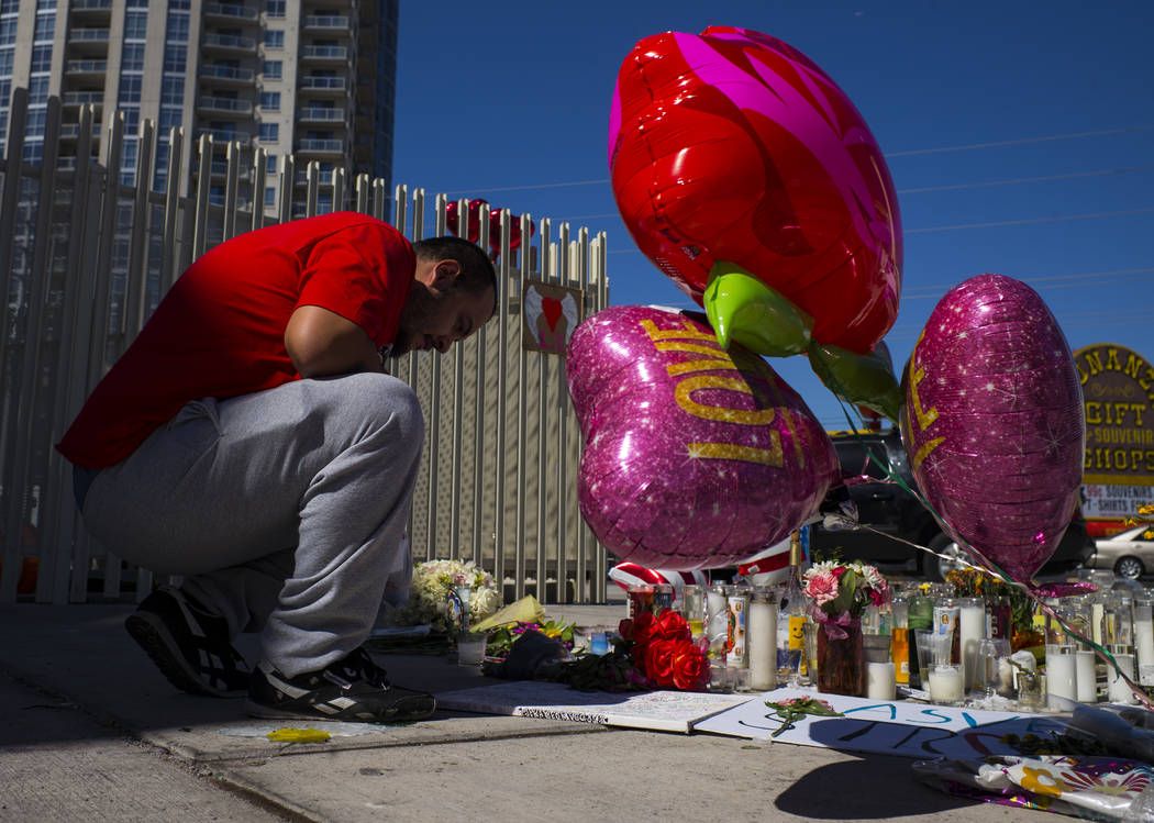 Las Vegas resident David Robles looks at items left at a memorial at Las Vegas Boulevard and Sahara Avenue in Las Vegas during the early hours of Tuesday, Oct. 3, 2017. A gunman opened fire on att ...