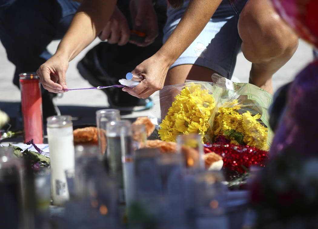 Jessica Yerkey of Ramona, Calif., who was at the Route 91 festival on Sunday, leaves her festival wristband behind at a memorial at Las Vegas Boulevard and Sahara Avenue in Las Vegas during the ea ...