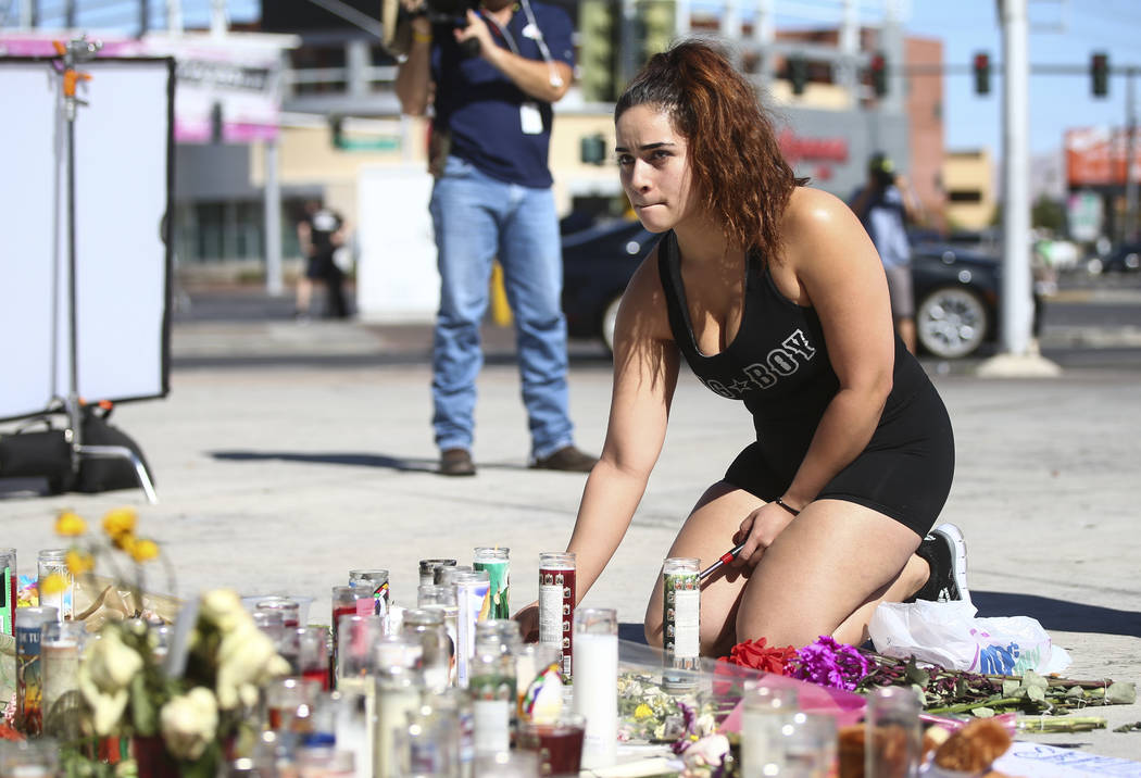 Las Vegas resident Jatziry Yanez lights a candle at a memorial at Las Vegas Boulevard and Sahara Avenue in Las Vegas during the early hours of Tuesday, Oct. 3, 2017. A gunman opened fire on attend ...