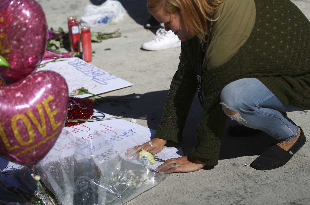 A woman leaves a letter and rose at a memorial at Las Vegas Boulevard and Sahara Avenue in Las Vegas during the early hours of Tuesday, Oct. 3, 2017. A gunman opened fire on attendees of a music f ...