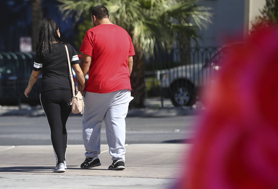 Las Vegas residents Elba Armendariz, left and David Robles leave after placing candles at a memorial at Las Vegas Boulevard and Sahara Avenue in Las Vegas during the early hours of Tuesday, Oct. 3 ...