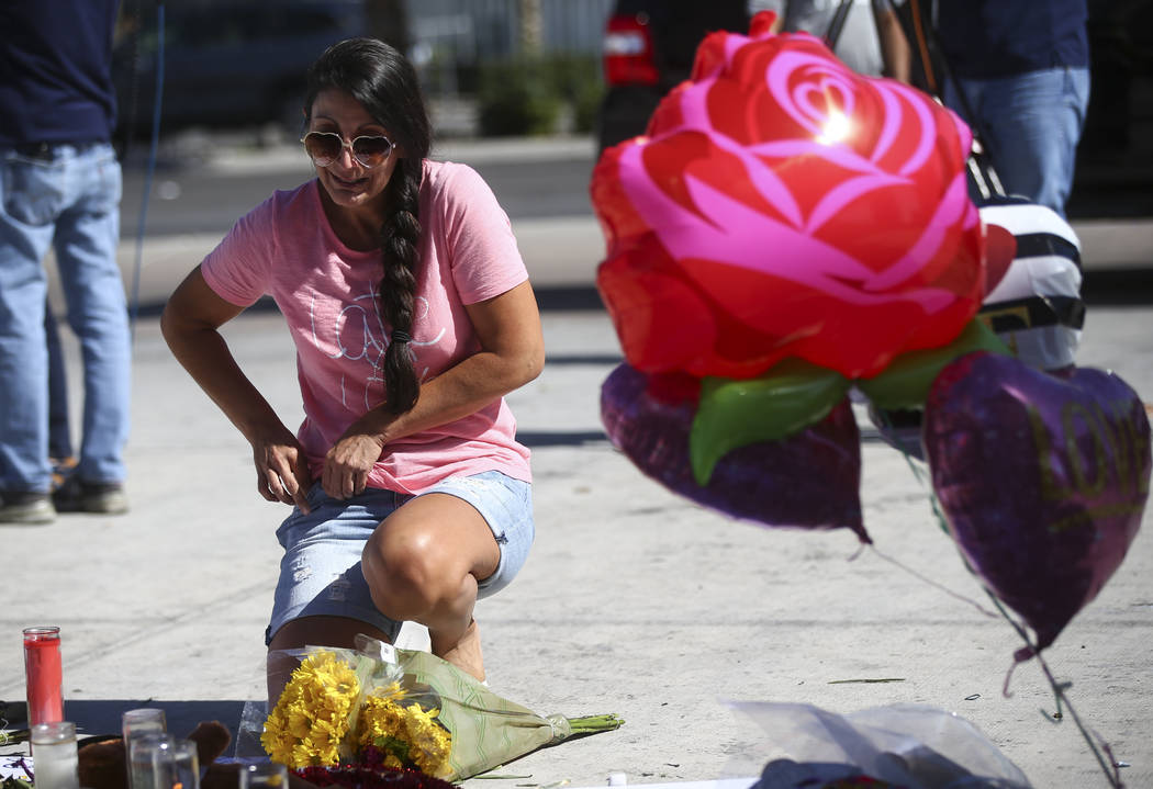 Jessica Yerkey of Ramona, Calif., who was at the Route 91 festival on Sunday, brings flowers to leave at a memorial at Las Vegas Boulevard and Sahara Avenue in Las Vegas during the early hours of  ...