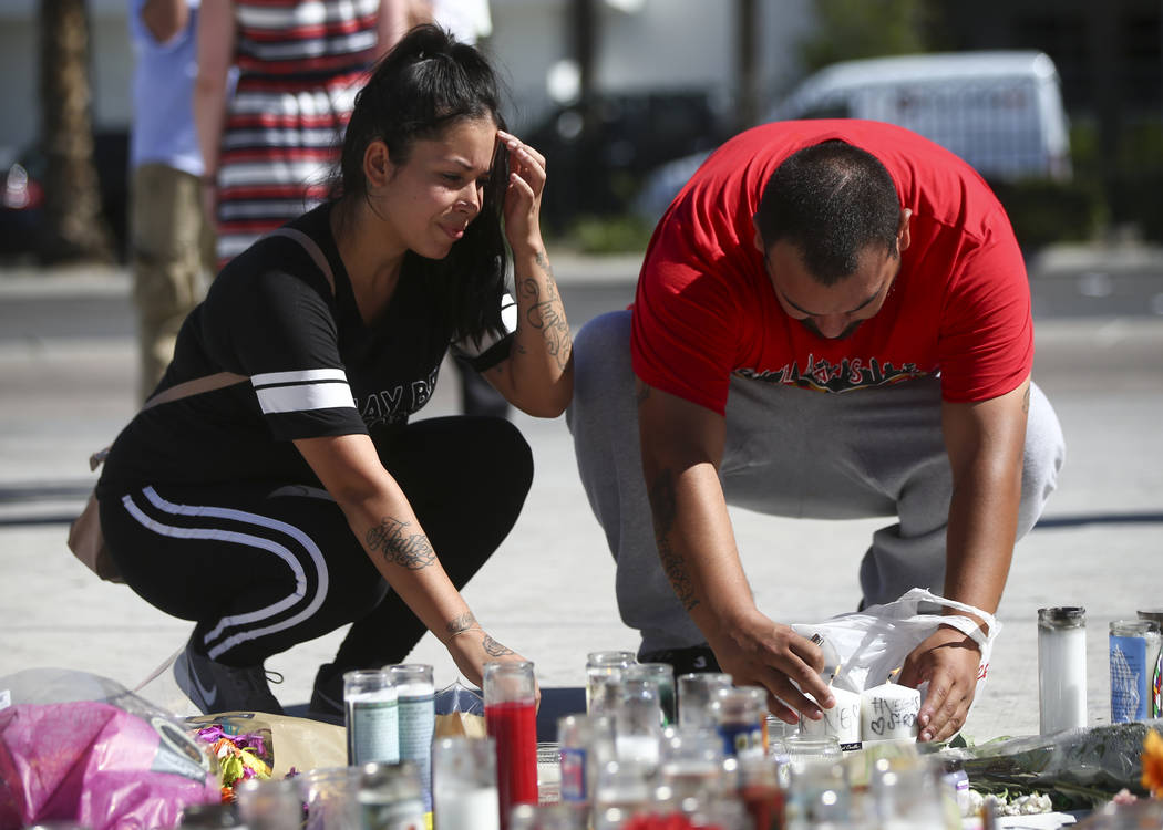 Las Vegas residents Elba Armendariz, left and David Robles leave candles at a memorial at Las Vegas Boulevard and Sahara Avenue in Las Vegas during the early hours of Tuesday, Oct. 3, 2017. A gunm ...