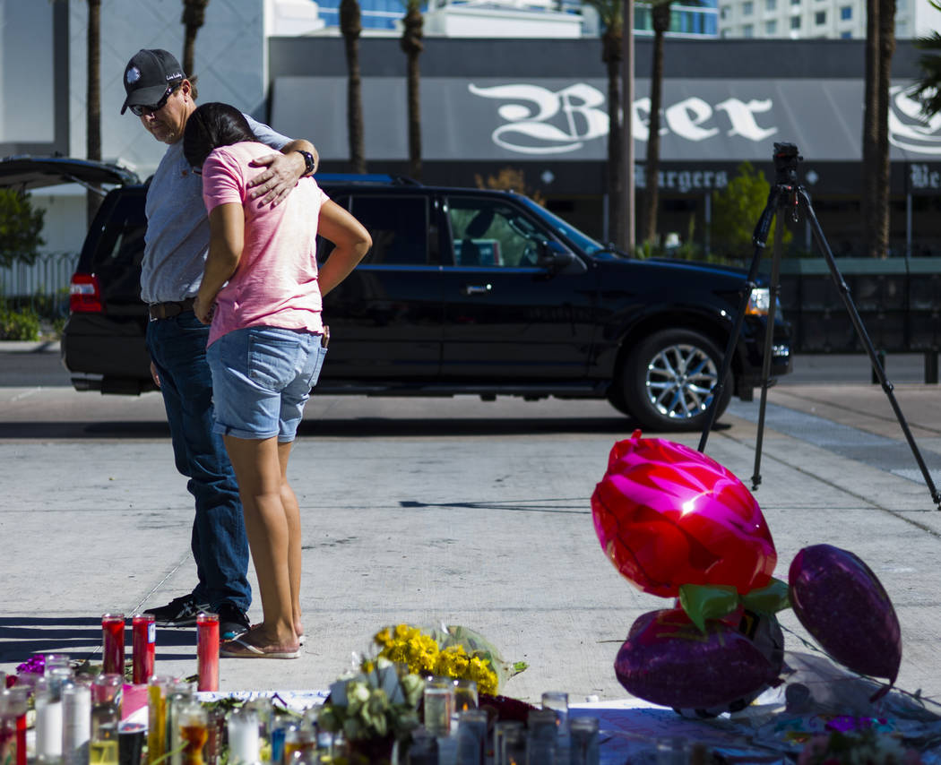 Mike and Jessica Yerkey of Ramona, Calif. pause at a memorial at Las Vegas Boulevard and Sahara Avenue in Las Vegas during the early hours of Tuesday, Oct. 3, 2017. A gunman opened fire on attende ...