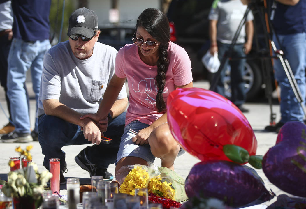 Mike and Jessica Yerkey of Ramona, Calif. pause at a memorial at Las Vegas Boulevard and Sahara Avenue in Las Vegas during the early hours of Tuesday, Oct. 3, 2017. Jessica, an attendee at the con ...