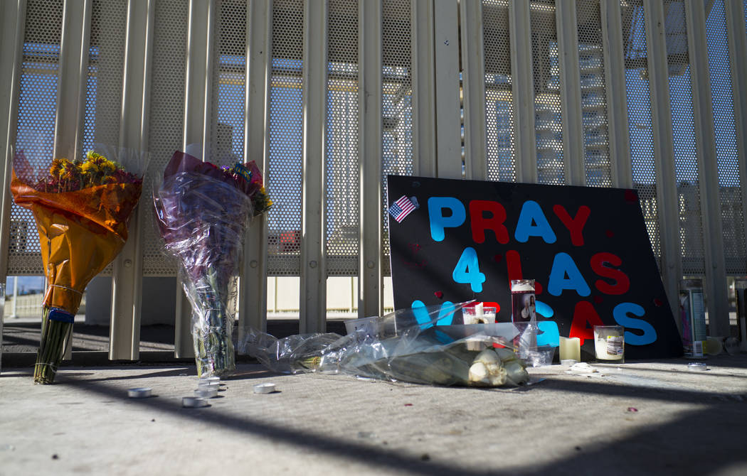 Signs, flowers and candles are some of many items left at a memorial at Las Vegas Boulevard and Sahara Avenue in Las Vegas during the early hours of Tuesday, Oct. 3, 2017. A gunman opened fire on  ...