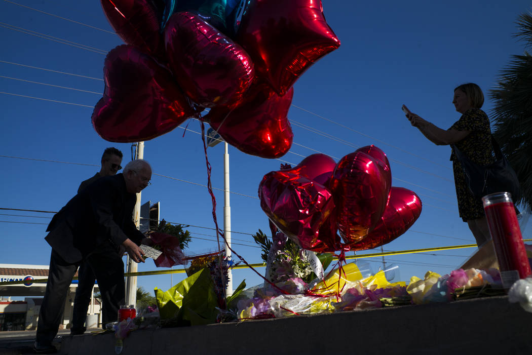 United States Conference of Mayors CEO and Executive Director Tom Cochran, left, places roses by a memorial at Las Vegas Boulevard and Reno Avenue outside of the Luxor, near the Route 91 music fes ...