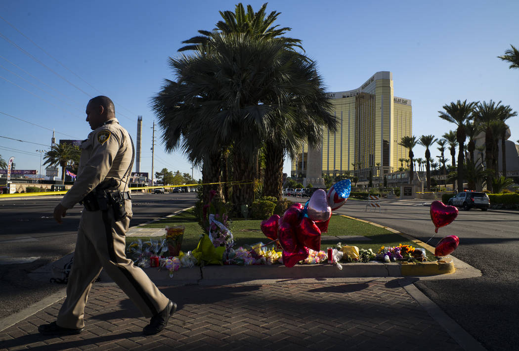 A Las Vegas police officer walks by a memorial at Las Vegas Boulevard and Reno Avenue outside of the Luxor, near the Route 91 music festival grounds in Las Vegas on Tuesday, Oct. 3, 2017. A gunman ...