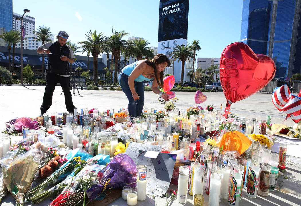Matthew Edwards, left, and Sharine Ramos light candles on Tuesday, Oct. 3, 2017 at a makeshift memorial for the shooting victims at the corner of Sahara Avenue and Las Vegas Boulevard in Las Vegas ...