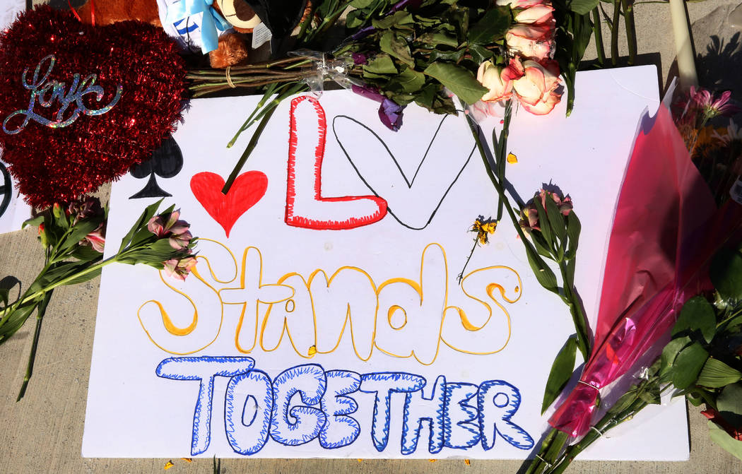 Flowers and a poster are placed at a makeshift memorial for the shooting victims at the corner of Sahara Avenue and Las Vegas Boulevard on Tuesday, Oct. 3, 2017, in Las Vegas. Bizuayehu Tesfaye La ...