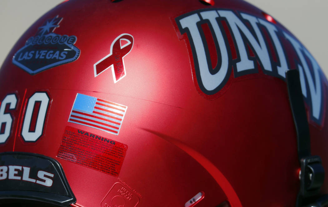 A ribbon inscribed with the words Las Vegas is illuminated on the back of the helmet of UNLV offensive lineman Andrew Erbes to commemorate the victims of the shooting massacre, as players warm up  ...