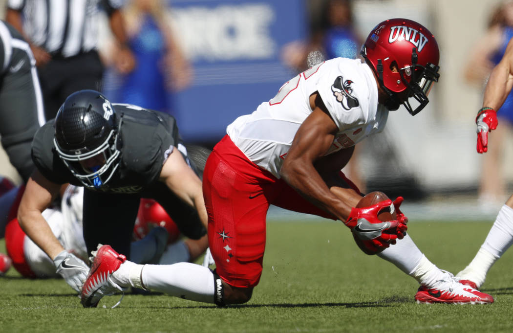 UNLV cornerback Jocquez Khalili, front, picks up a fumble from Air Force running back Nolan Eriksen in the second half of an NCAA college football game, Saturday, Oct. 14, 2017, at Air Force Acade ...