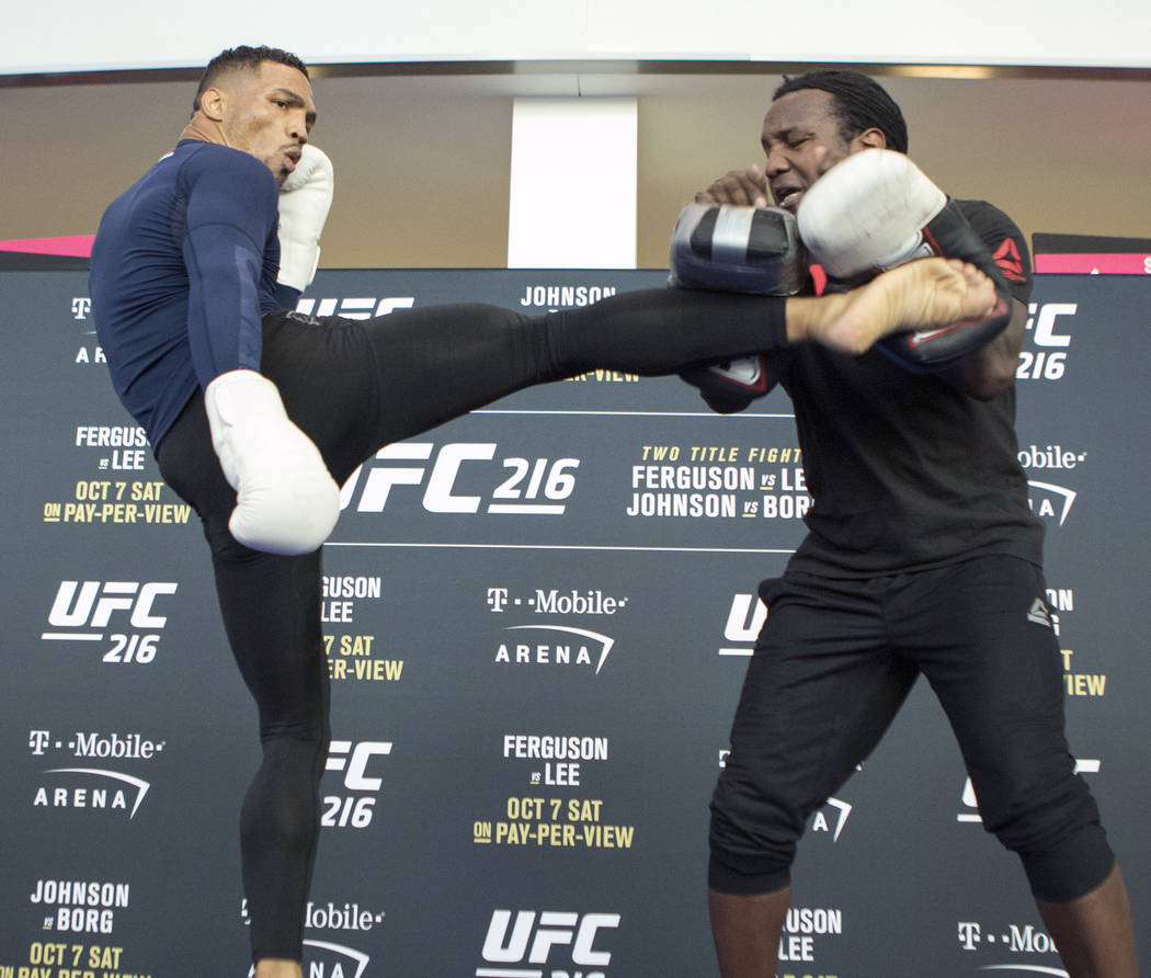 UFC lightweight title contender Kevin Lee, left, kicks pads with his coach Dewey Cooper at the T-Mobile Arena during UFC 216 open workouts in Las Vegas, Thursday, Oct. 5, 2017. Heidi Fang Las Vega ...