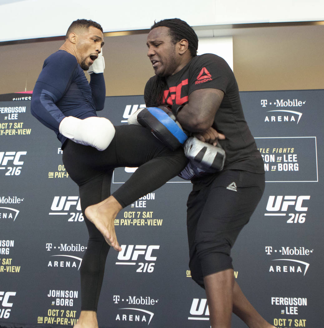 UFC lightweight title contender Kevin Lee, left, hits pads with his coach Dewey Cooper at the T-Mobile Arena during UFC 216 open workouts in Las Vegas, Thursday, Oct. 5, 2017. Heidi Fang Las Vegas ...