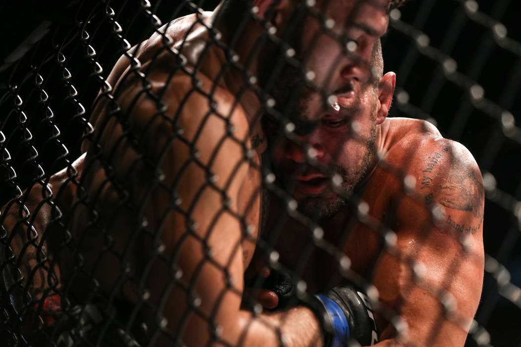 Brad Tavares, left, is pressed against the fence by Thales Leites, right, during the third round of the preliminary middleweight bout of UFC 216 at T-Mobile Arena in Las Vegas, Saturday, Oct. 7, 2 ...