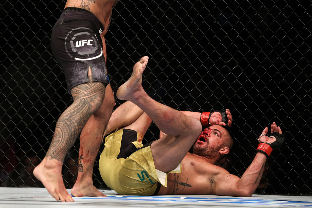 Brad Tavares, left, prepares to punch Thales Leites, right, as he lies on the ground during the third round of the preliminary middleweight bout of UFC 216 at T-Mobile Arena in Las Vegas, Saturday ...