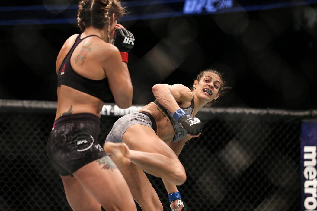 Pearl Gonzalez, left, is kicked by Poliana Botelho, right, during the second round of the preliminary womenճ strawweight bout of UFC 216 at T-Mobile Arena in Las Vegas, Saturday, Oct. 7, 201 ...