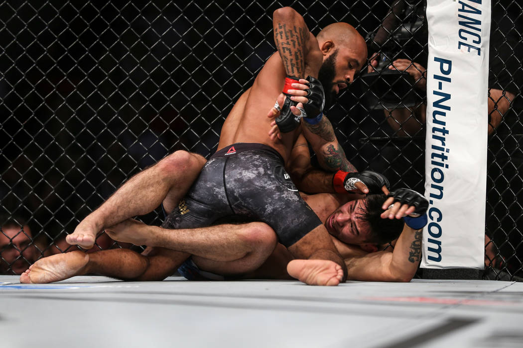 Demetrious Johnson, top, presses down Ray Borg, bottom, during the world flyweight championship bout UFC 216 at T-Mobile Arena in Las Vegas, Saturday, Oct. 7, 2017. Johnson won by submission. Joel ...