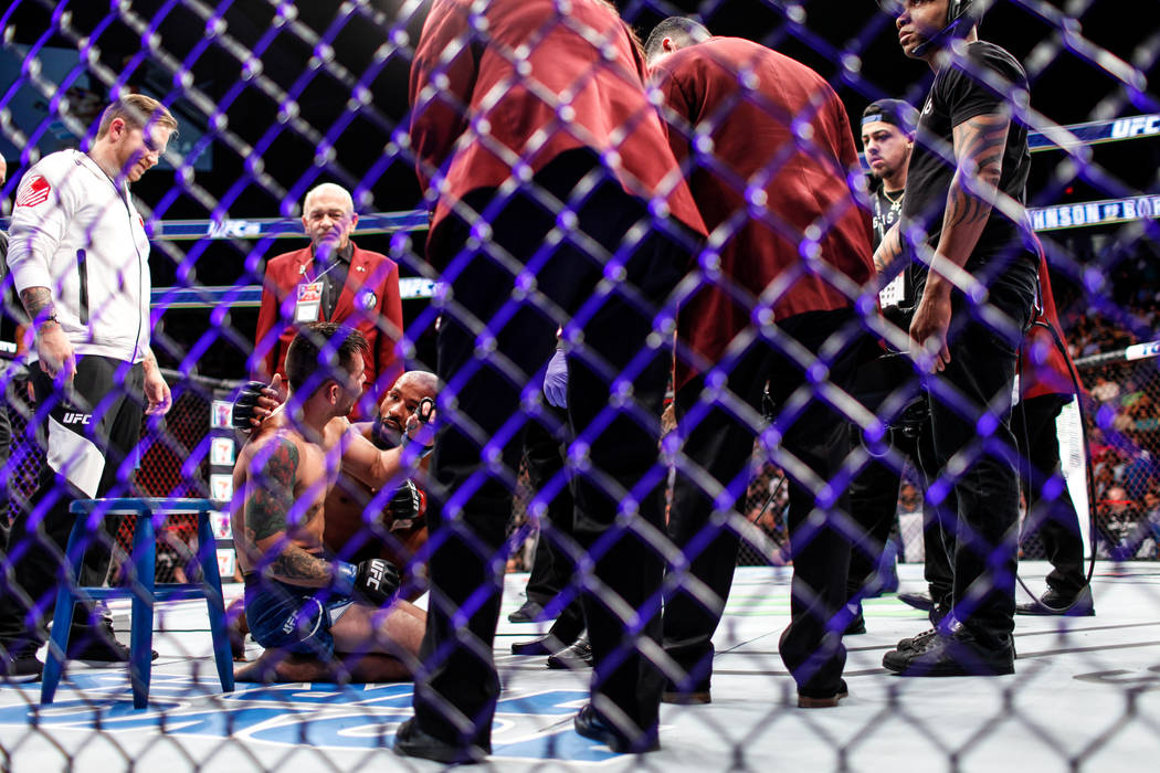 Ray Borg, left, is comforted by Demetrious Johnson, right, after losing the world flyweight championship bout UFC 216 at T-Mobile Arena in Las Vegas, Saturday, Oct. 7, 2017. Johnson won by submiss ...