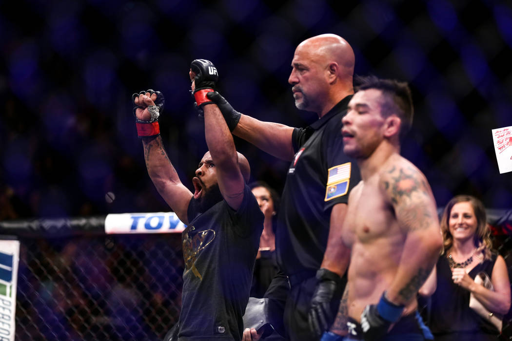 Demetrious Johnson, left, celebrates after defeating Ray Borg, right, in the world flyweight championship bout UFC 216 at T-Mobile Arena in Las Vegas, Saturday, Oct. 7, 2017. Johnson won by submis ...
