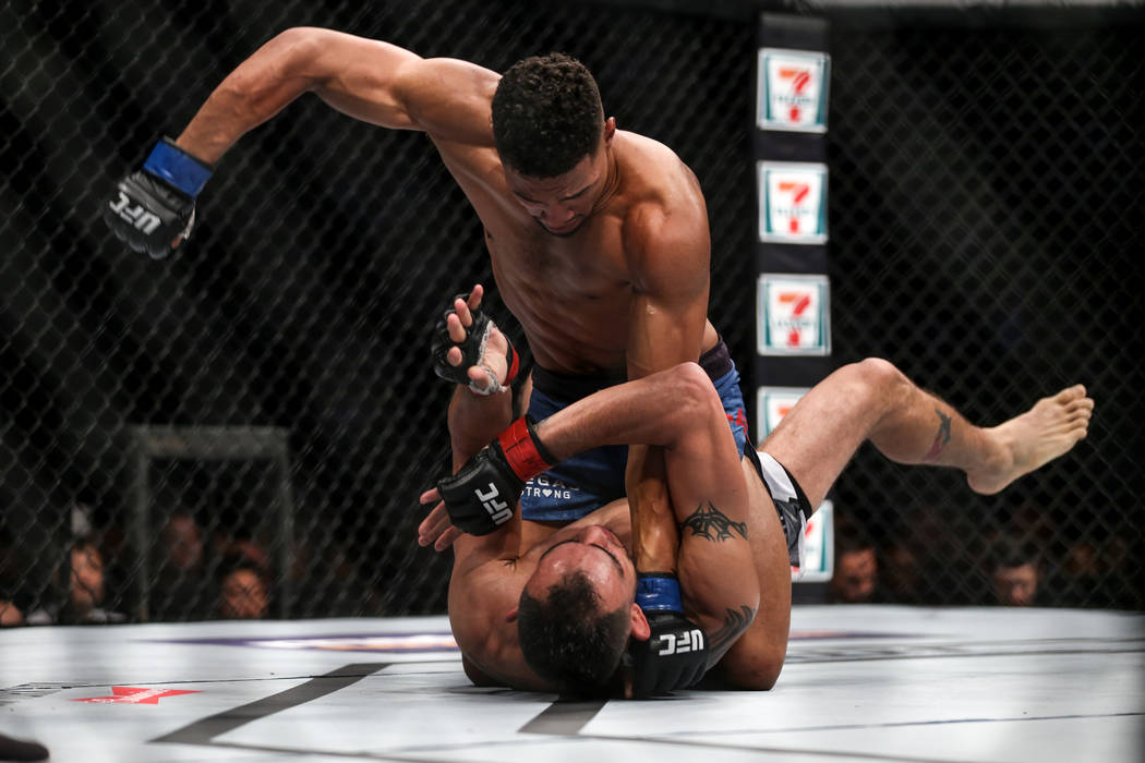 Kevin Lee, top, punches Tony Ferguson, bottom, during the interim lightweight championship bout UFC 216 at T-Mobile Arena in Las Vegas, Saturday, Oct. 7, 2017. Ferguson won by submission. Joel Ang ...