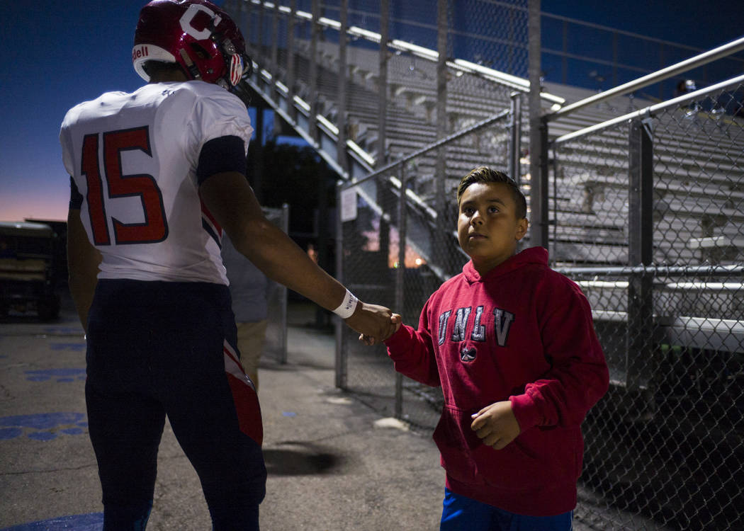 Coronado's Ayzayah Hartfield (15), son of fallen Las Vegas police officer Charleston Hartfield, gets a high-five from a young fan before a football game at Basic High School in Henderson on Friday ...