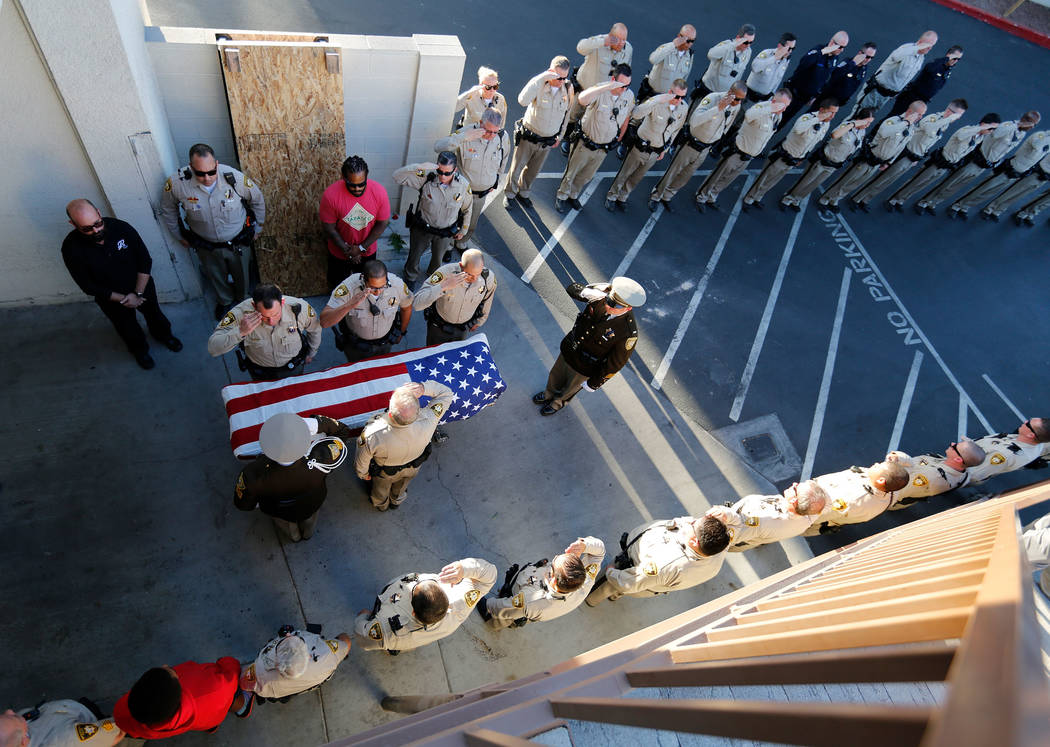 Metropolitan Police Department officers salute the casket of officer Charleston Hartfield on Tuesday, Oct. 3, 2017, as his it arrives at Palm Downtown Mortuary and Cemetery in Las Vegas. Hartfield ...