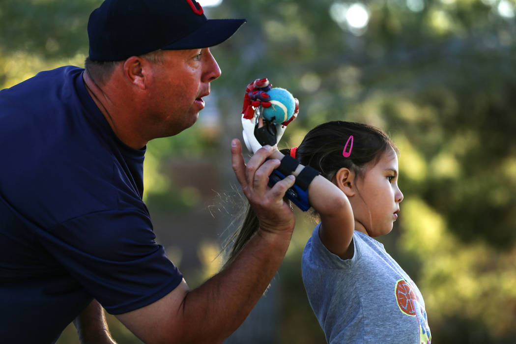Coach Tom Hallett, 48, left, and Hailey Dawson, 7, right, both living in Henderson, practice Dawson's pitch for the MLB World Series opener during a session at Anthem Hills Park in Henderson, Thur ...