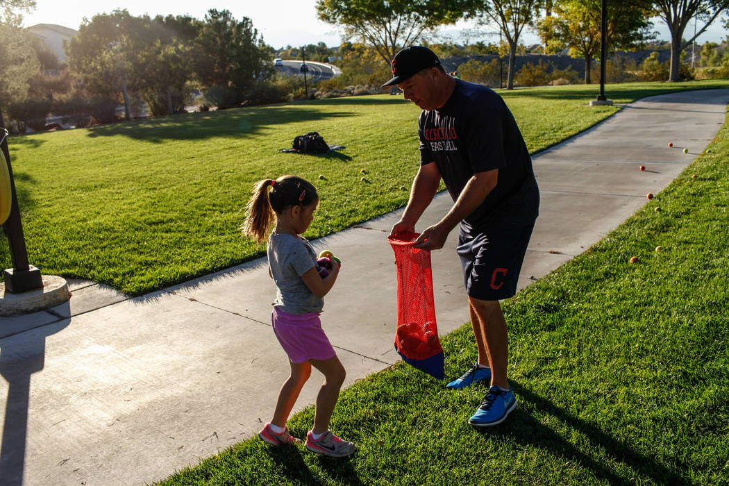 Hailey Dawson, 7, left, and one of her coaches Tom Hallett, 48, both living in Henderson, gather baseballs as Dawson practices her pitch for the MLB World Series opener during a session at Anthem  ...