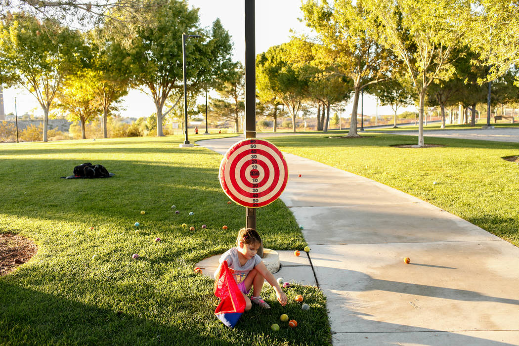 Hailey Dawson, 7, of Henderson, gathers baseballs as she practices her pitch for the MLB World Series opener during a session at Anthem Hills Park in Henderson, Thursday, Oct. 19, 2017. A group of ...