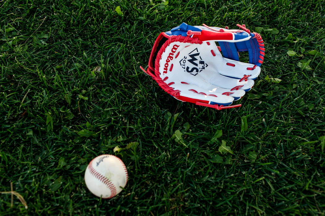 An MLB World Series themed baseball glove belonging to Hailey Dawson, 7, of Henderson, lays on the ground during a practice at Anthem Hills Park in Henderson, Thursday, Oct. 19, 2017. A group of r ...